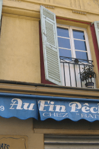 A blue awning, hangs above a yellow restaurant